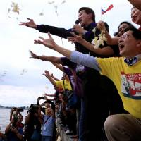 Protesters throw flowers while chanting anti-Chinese slogans during a rally by different activist groups over the South China Sea dispute, along a bay in Manila on Tuesday. | REUTERS