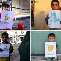 A combination photo shows boys holding pictures depicting Pokemon characters. The photos (clockwise from top right) show boys holding banners reading: 'I am from Kafr Naboudah, save me!' 'I am in Kafr Nabl in rural Idlib, come and save me!' 'I am in Eastern Ghouta in Syria, come and get me!' and 'I am trapped in Douma in Eastern Ghouta, Help me.'   REUTERS