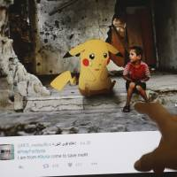 A journalist looks at a montage by Syrian artist Moustafa Jano using the international frenzy over the 'Pokemon Go' game to draw new attention to the battle-scarred country.   AFP-JIJI