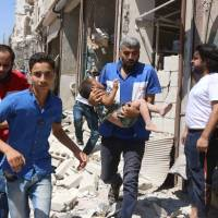 A Syrian carries a boy wounded in an airstrike on the rebel-held Aleppo neighborhood of Qatirji on Saturday.   AFP-JIJI