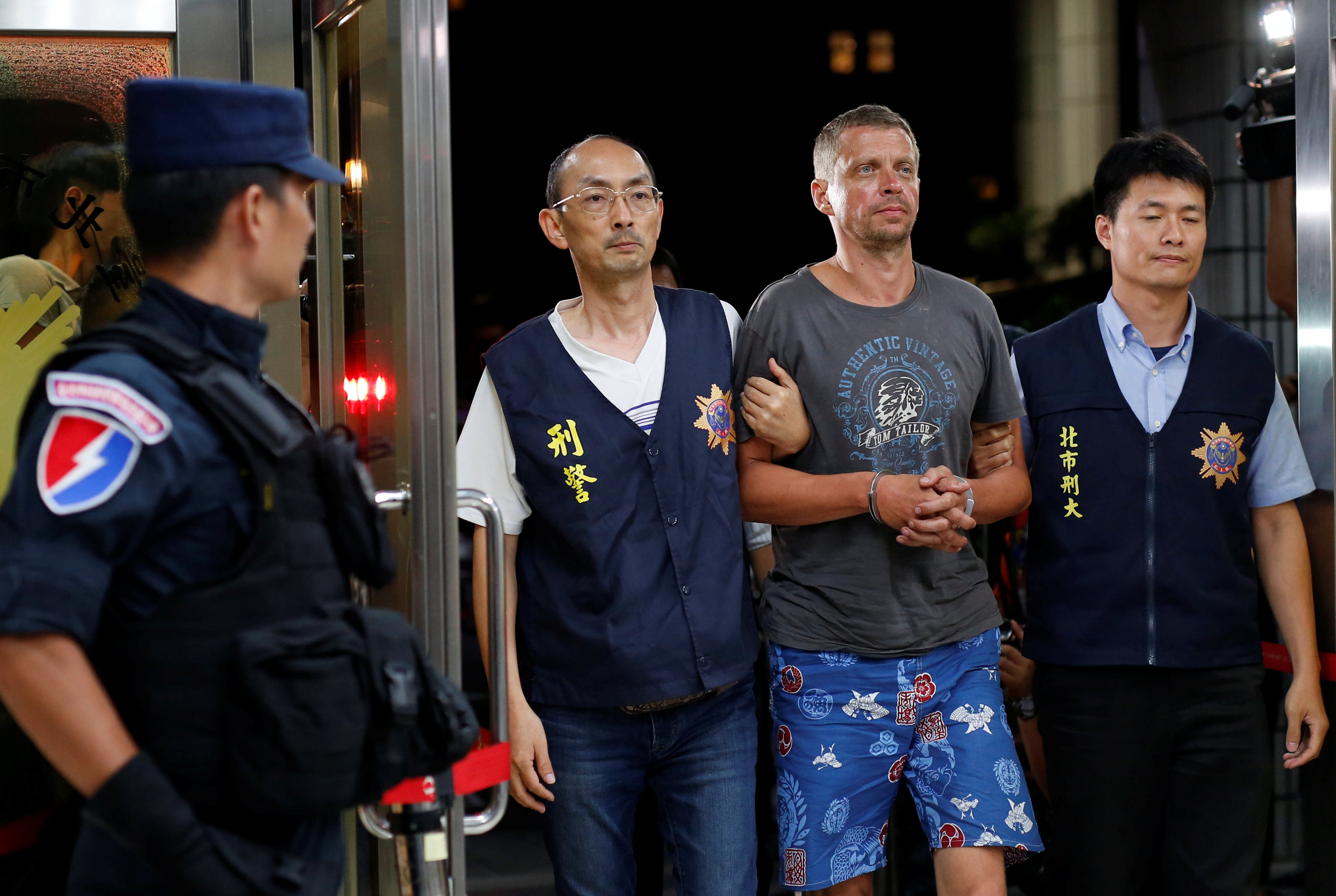 Andrejs Peregudovs from Latvia, who is suspected of stealing from an automated teller machine, is escorted at the police station in Taipei Sunday.   REUTERS