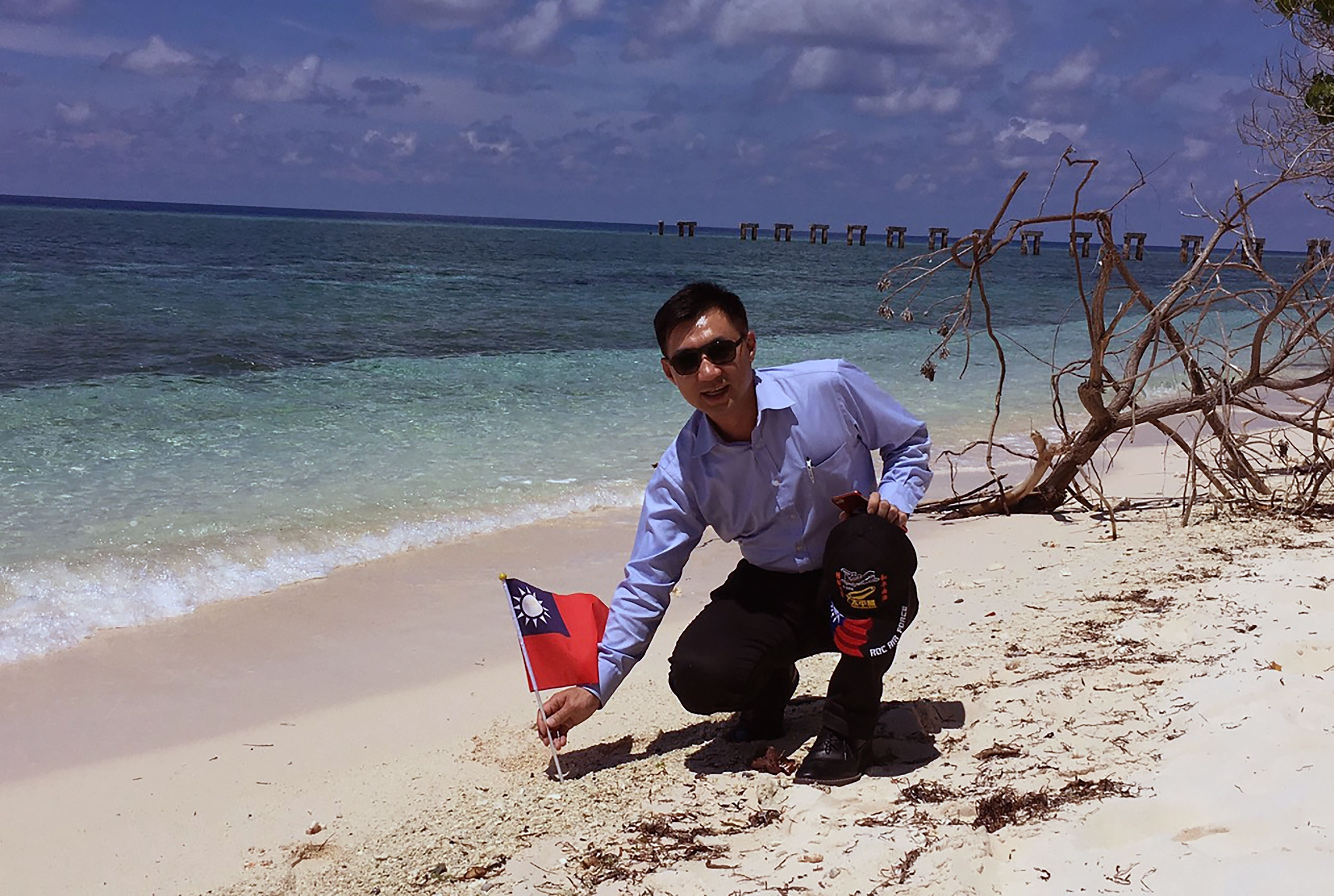 This handout picture taken and released Wednesday by the office of Kuomintang (KMT) lawmaker Johnny Chiang shows  Chiang holding a Taiwanese flag during a visit to Taiping island in the South China Sea. | THE OFFICE OF KUOMINTANG (KMT) LAWMAKER JOHNNY CHIANG / AFP-JIJI