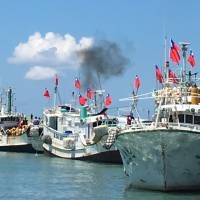 Taiwanese fishing boats flying national flags prepare to leave for the Taiwan-controlled Taiping Island from Taiwan's southern port city of Pingtung Wednesday. In Taiwan — one of six sides with territorial claims in the South China Sea — eight legislators from the ruling and main opposition parties flew aboard an air force transport plane Wednesday to Taiping Island, Taiwan's sole holding in the disputed Spratly Island chain. | CENTRAL NEWS AGENCY VIA AP