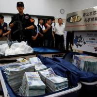 Taiwanese banknotes are displayed after they were found in a hotel room rented by one of the suspects involved in stealing from automated teller machines (ATM) in Taipei Sunday.   REUTERS