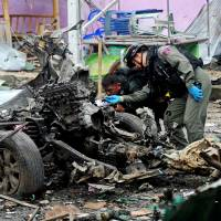 Bomb experts inspect evidence after a car bomb struck in Sungai Kolok, a district in the separatist south of Thailand, on June 26. More than 6,500 people have died in clashes since 2004. | AFP-JIJI