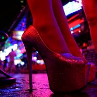 Women stand outside a bar in a red light district in Bangkok on July 12. | REUTERS