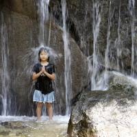 A girl stands under a waterfall like a meditating Buddhist monk in the water fountain at Asuka Park in Tokyo amid high temperatures Monday.   AP