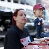 A woman walks by a bobblehead for sale of Republican presidential candidate Donald Trump, Sunday in Cleveland. The Republican National Convention starts Monday in Cleveland.   AP