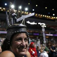A delegate wears a 'Trump's Wall: Latins Keep Out!!!' hat on the floor during the second day of the Democratic National Convention in Philadelphia Tuesday. | REUTERS