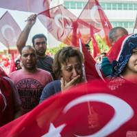People wave Turkish flags after a military position was retaken at Istanbul Ataturk Airport on Saturday.   AFP-JIJI