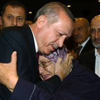 Turkish President Recep Tayyip Erdogan hugs a woman during an event in Ankara on Friday to honor those killed or wounded during the July 15 coup attempt. | AP