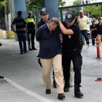 Police officers escort Adm. Atilla Demirhan and a group of millitary personal detained in Mersin, Turkey, Tuesday. | DEPO PHOTOS VIA AP