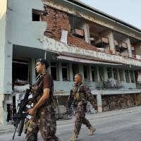 Turkish special forces policemen walk in front of their damaged base, which was attacked by the Turkish warplanes during the failed military coup last Friday, in Ankara Tuesday. The violence surrounding the Friday night coup attempt claimed the lives of 208 government supporters and 24 coup plotters, according to the government. | AP