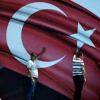 Personnel prop up a stage backdrop before a pro-government demonstration in an Istanbul park on Tuesday. | REUTERS
