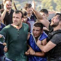 Turks on Istanbul's Bosporus Bridge apprehend a soldier who participated in the attempted military coup on Saturday. | AP