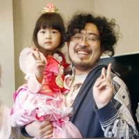 Shunsuke Wada poses with his daughter at an anime event in the city of Oyabe, Toyama Prefecture, in March. | KYODO