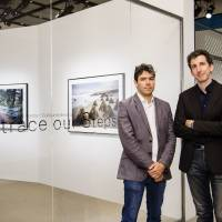 Photographers Carlos Ayesta (left) and Guillaume Bression pose in front of their 'Retrace Our Steps' photo exhibition at Chanel Nexus Hall in Tokyo's Ginza district. | COURTESY OF CHANEL K.K./KYODO