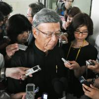 Okinawa Gov. Takeshi Onaga faces reporters at Naha Airport in Okinawa Prefecture on June 23. | KYODO