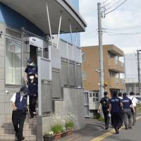 Public Security Intelligence Agency officers leave Aleph's new operating base in Sapporo after investigating the building on Thursday. | KYODO