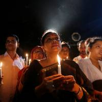 People attend a candlelight vigil for victims of the Dhaka attack in Bangladesh's capital late Sunday. | REUTERS