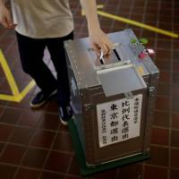 A voter casts his ballot for Japan's Upper House election at a polling station in Tokyo on Sunday. | REUTERS