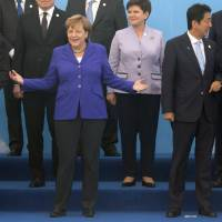 German Chancellor Angela Merkel (center) stands between Chinese Premier Li Keqiang (left) and Prime Minister Shinzo Abe as they pose for a group photo at the 11th Asia-Europe Meeting (ASEM) in Ulaan Baatar, Mongolia, on Friday.   AP
