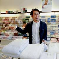 Eight One Co. managing director Yuji Murakami shows off high-quality Iori towels in Matsuyama, Ehime Prefecture, in this photo taken in May. | KYODO