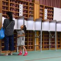 A mother casts a ballot in the Upper House election Sunday at a polling station in Tokyo's Suginami Ward, as her daughter looks on. | SATOKO KAWASAKI