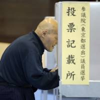 A man votes Sunday at a polling station in Tokyo. Exit polls suggested the ruling bloc might win big. | AP
