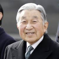 Emperor Akihito is seen at Haneda airport in Tokyo on Jan. 26 before flying to the Philippines. With him is Crown Prince Naruhito. On the five-day visit, the Emperor paid tribute to warm bilateral ties that grew from the ashes of World War II. | AP