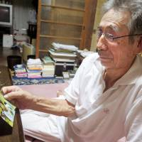Nobuyuki Noguchi looks at a picture of his daughter, Takako, on Thursday. She was hospitalized after being attacked at a residential care facility for people with disabilities in Sagamihara, Kanagawa Prefecture, on Tuesday. | KYODO