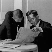 Emperor Hirohito and his son, Akihito, read the U.S. military's Stars and Stripes newspaper in a photo taken in December 1945. | JAPAN CAMERA INDUSTRY INSTITUTE / VIA KYODO