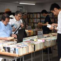 People browse used volumes at one of some 160 bookstores in Jinbocho in Tokyo's Chiyoda Ward.   SATOKO KAWASAKI