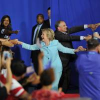 Democratic U.S. presidential candidate Hillary Clinton and her running mate, Sen. Tim Kaine, arrive for a campaign rally at Florida International University in Miami on Saturday. | AFP-JIJI