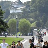 Tourists visit the Imperial Palace in Tokyo on July 14.   KYODO