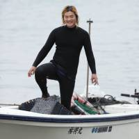 Free diver Yushi Ikeda returns from fishing with his female colleagues in Shima, Mie Prefecture, on June 19. | KYODO