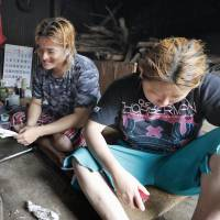 Free diver Yushi Ikeda (center) chats with his wife and fellow diver, Mana (right), 20, and veteran diver Noriko Minami in a hut in Shima, Mie Prefecture, on June 20. | KYODO
