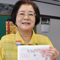 Naha Mayor Mikiko Shiroma shows a certificate for same-sex couples at the municipal government building Wednesday. | KYODO