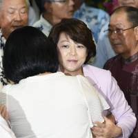 Aiko Shimajiri, state minister in charge of Okinawa affairs, is consoled by a supporter in Naha, Okinawa Prefecture, on Sunday after her defeat. | KYODO
