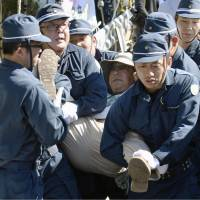 Police take away a protester opposed to U.S. helipad construction in the village of Higashi in Okinawa on Friday. | KYODO