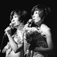 Yumi Ito (right) and Emi Ito of the twin pop duo Peanuts appear on stage in 1975. | KYODO