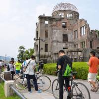 Smartphone gamers play 'Pokemon Go' near the Atomic Bomb Dome in Hiroshima on Tuesday.   KYODO