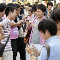 Young people play 'Pokemon Go' in the Akihabara district of Tokyo on Saturday. | KYODO