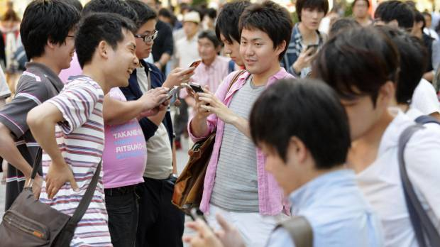 "Young people play ""Pokemon Go"" in the Akihabara district of Tokyo on Saturday."