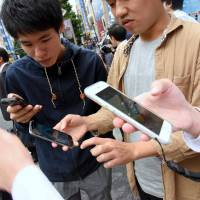 People play 'Pokemon Go' in Tokyo's Akihabara district hours after the game's domestic launch on Friday. | SATOKO KAWASAKI