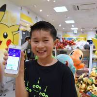 A boy shows off a smartphone displaying the action from a 'Pokemon Go' game at a Pokemon goods shop in Tokyo on Friday. | SATOKO KAWASAKI