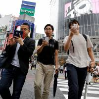 People play the augmented reality game 'Pokemon Go' on their mobile phones as they cross a busy street in Shibuya on Friday.   REUTERS