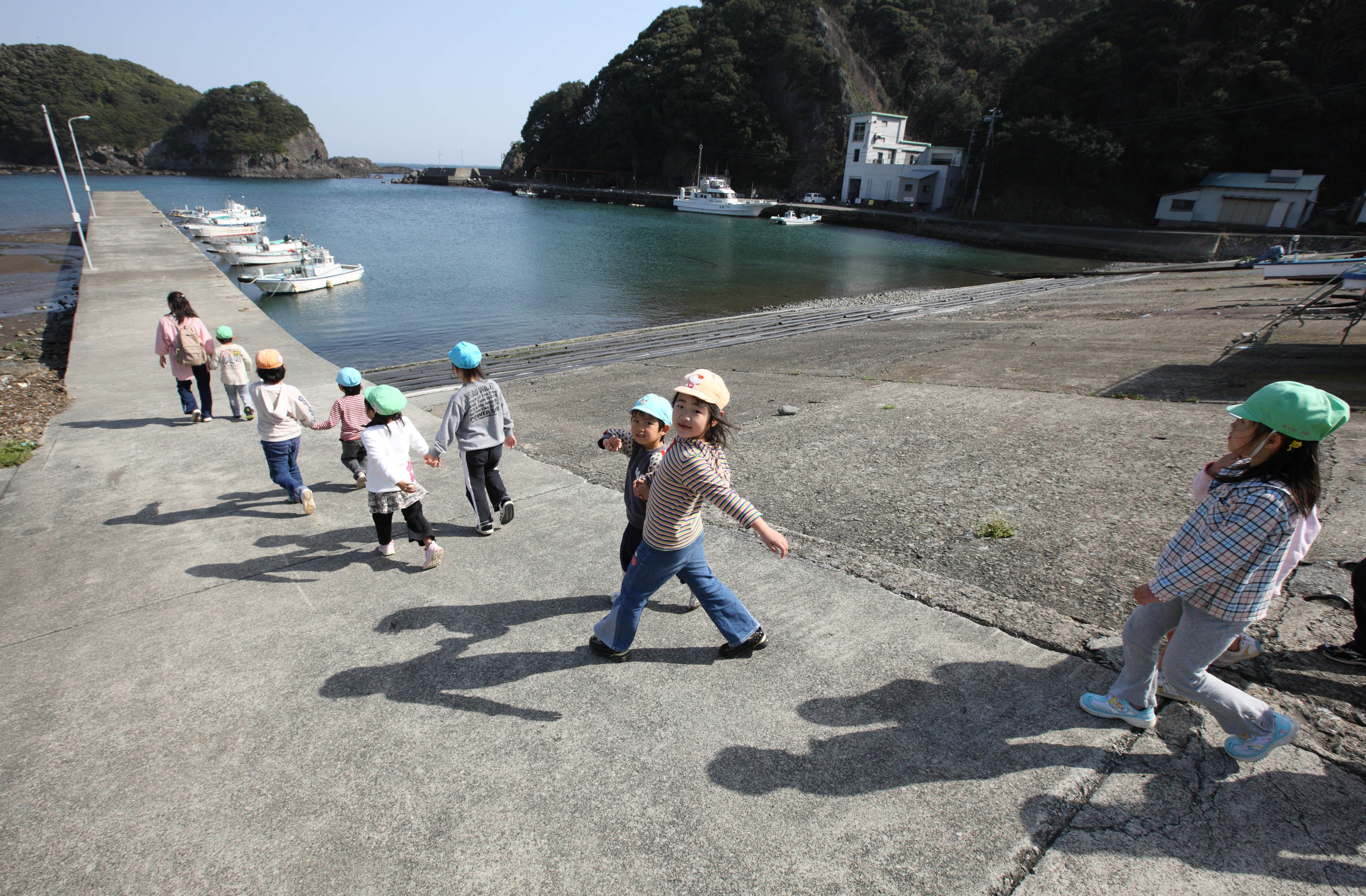 Children walk along a pier in the town of Minami-Izu, Shizuoka Prefecture. A government survey showed Wednesday that Japan's population as of Jan. 1 dropped at the fastest pace ever on an annual basis. | BLOOMBERG