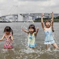 Children play in the water at a beach in Tokyo's Odaiba area on Thursday when the weather agency announced the rainy season in the Kanto region is believed to have ended.   KYODO