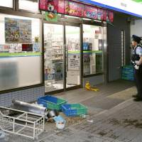 Police investigate the scene of a rampage perpetrated by young men outside a convenience store in Kobe's Suma Ward Sunday evening. | KYODO